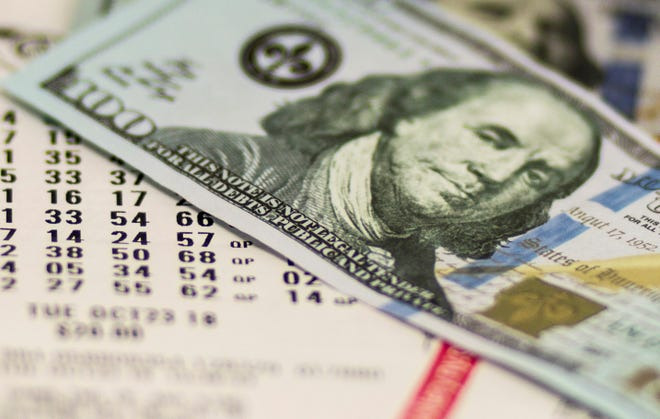 Lotto tickets are covered with one hyndred dollar bills.