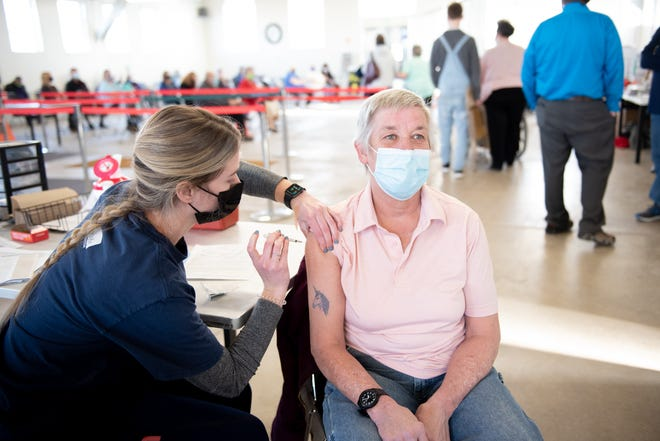 Benefis nurse Kayla VanderKooy gives Great Falls resident Tanya Schaefer the 10,000th vaccine administered at the Cascade County Community COVID-19 Vaccination Clinic.