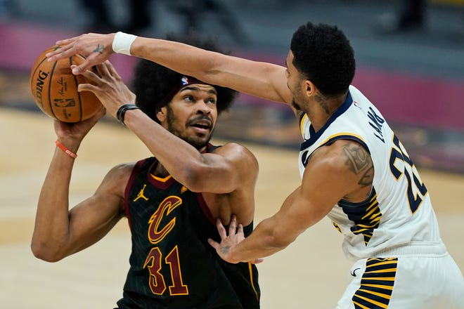 Cleveland Cavaliers' Jarrett Allen, left, is defended by Indiana Pacers' Jeremy Lamb (26) during the first half of an NBA basketball game Wednesday, March 3, 2021, in Cleveland.