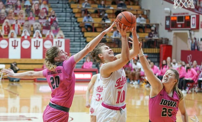 Indiana's Aleksa Gulbe (10) attempts a shot between Iowa's Kate Martin (20) and Monika Czinano (25) during Wednesday's game at Simon Skjodt Assembly Hall.