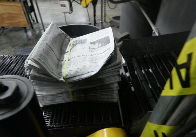 A bundle of newspapers go down a conveyor belt of the print edition for that evening's Courier Journal on March 1, 2021.