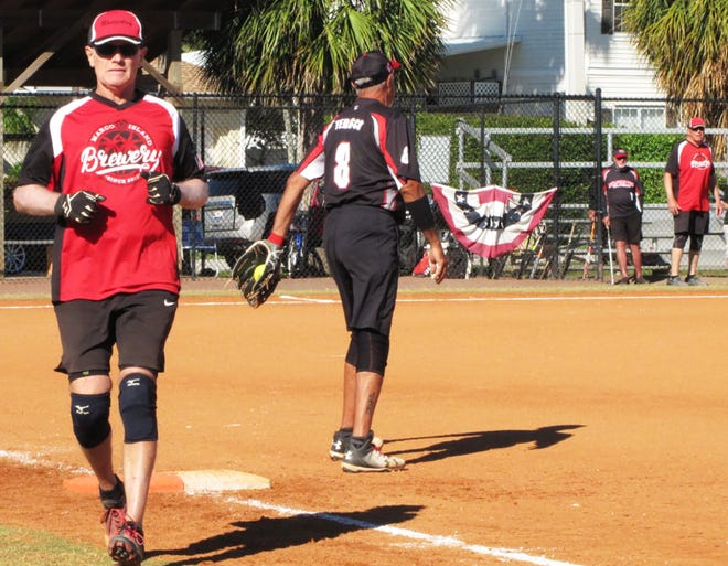 Brewery's Gary Grefer is out on a play at first base by Dolphin Tiki's Frank Tedesco.