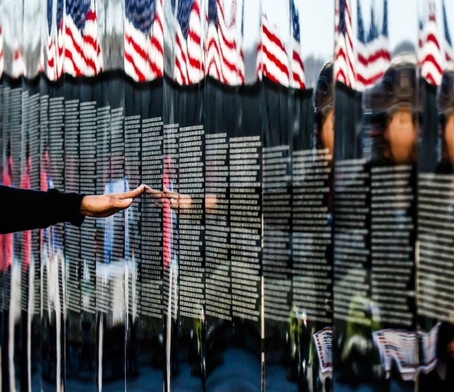 Marcia Turner of Oconomowoc reaches out to the name of her cousin, Jack D. Downs, while visiting The Moving Wall at Crosspoint Community Church in Oconomowoc on Nov. 14, 2015.
