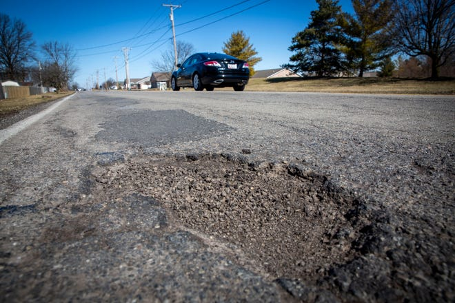 Potholes dot the sides of the road along North Walnut Street on Thursday, March 4, 2021. Potholes can be reported using the City of Muncie website.