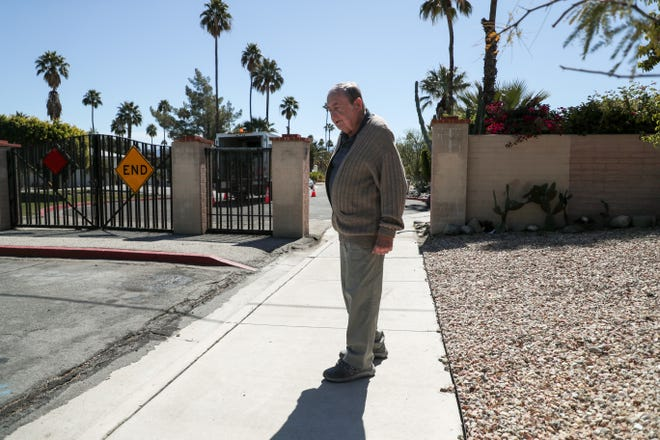 Jim Berry stands on the sidewalk after walking from his home and passing through the now open pedestrian gate on Rodeo Road in Palm Springs, Calif. on Thursday, March 4, 2021. The Palm Springs City Council unanimously approved modifying the gates in the El Mirador neighborhood on Feb. 12 despite opposition from residents in the area.