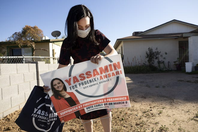 Yassamin Ansari, a Phoenix City Council District 7 candidate, fixes a yard sign while walking the Maryvale neighborhood of Phoenix to talk to potential supporters on March 1, 2021. Ansari is running against Cinthia Estela for the District 7 seat.