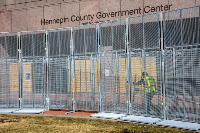 A worker installs security fencing at the Hennepin County Government Headquarters in Minneapolis, Minnesota, on March 3, 2021. Security measures are being increased and expected to see more police and National Guard soldiers in downtown Minneapolis before jury selection begins at the trial of former Minneapolis Police officer Derek Chauvin in George Floyd's death on March 8.