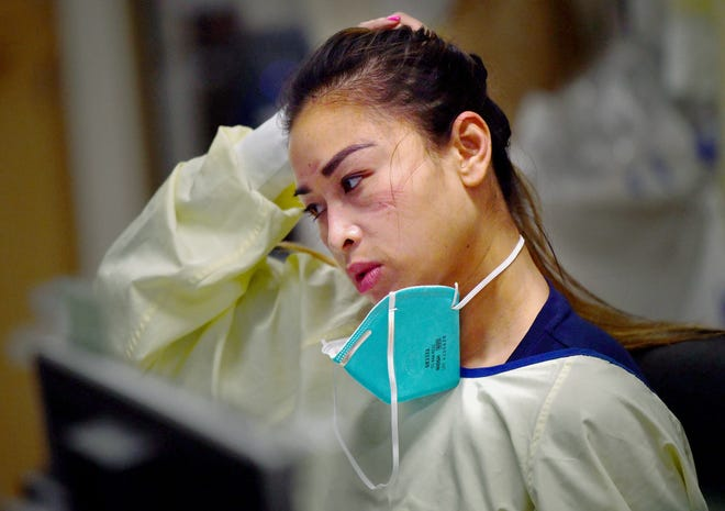 Travel nurse Thu Nguyen catches her breath inside the ICU unit at Providence Holy Cross Medical Center in Los Angeles on Tuesday, Feb. 9, 2021. Nurses are required to wear PPE for hours at a time while working with patients, sometimes causing bruises or scars around their eyes and nose.
