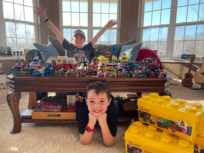 "Harrison Krauss, 7, (bottom) and Justice Krauss, 10 (above) pose with their LEGO world, Woof Woof Doggy Bone. Their LEGO journey began as a result of the pandemic. Stephanie Krauss, the boys' mother, said it's pretty remarkable that their LEGO world has taken a life of its own. ""The freedom of play that they have gotten is what I would have hoped for them,"" Krauss said."