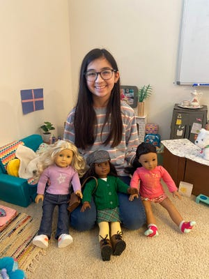 Reina Ushiroda, surrounded by her American Girl dolls and the cardboard furniture she created