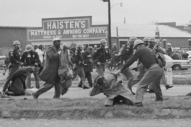 A state trooper swings a billy club at John Lewis, right foreground, chairman of the Student Nonviolent Coordinating Committee, to break up a civil rights voting march in Selma, Ala. on March 7, 1965.