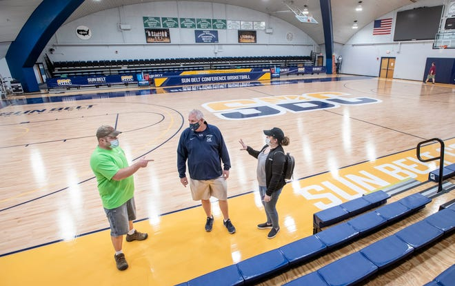 Doug Rogers, center, the facilities manager at Pensacola State College, talks Thursday with Rob Rottier and Casey Wilson of a Chattanooga, Tenn., flooring company about the installation of the court in advance of the Sun Belt women's basketball tournament at Hartsell Arena.