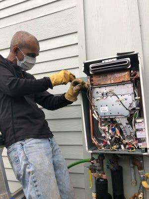 Ramesh Yerraballi works to fix a tankless water heater.
