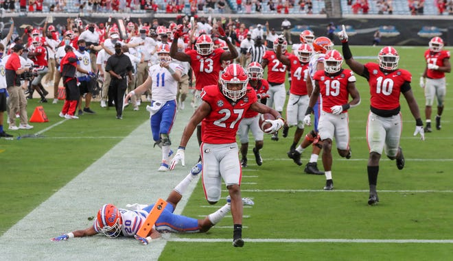 Georgia defensive back Eric Stokes (27) returns an interception for touchdown during the second quarter of a NCAA college football against Florida, Saturday, Nov. 7, 2020, in Jacksonville, Fla. (Curtis Compton/Atlanta Journal-Constitution via AP)