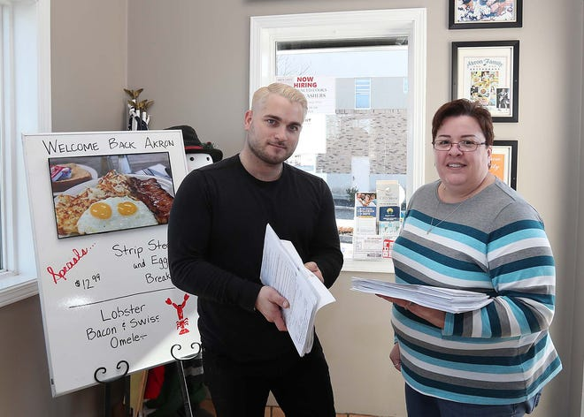 Nicholas Corpas, left, whose family owns Akron Family Restaurant, and Joyce Hurst, the restaurant's bookkeeper, hold the fraudulent unemployment claims they have received.