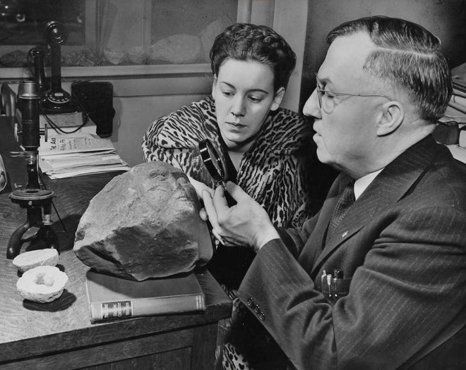 Walter A. Cook, a chemistry professor at the University of Akron, inspects a stone face March 29, 1949, with Evelyn Frost Melton, who purchased the carved rock for 50 cents from a 6-year-old neighbor on Sherman Street.