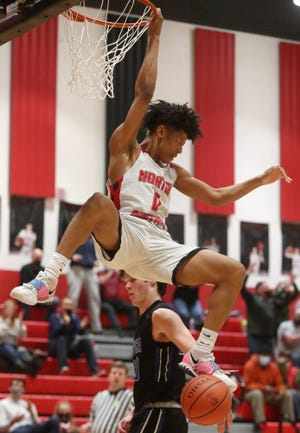 Norton's Tommy Reynolds hangs on the rim after a dunk against Cuyahoga Valley Christian Academy in a Division II district semifinal Thursday night at Norton. Reynolds had 25 points, nine rebounds and nine assists to lead the Panthers to a 75-45 win. [Mike Cardew/Akron Beacon Journal]