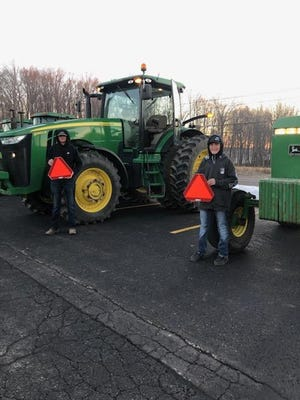 United High School students hold the reflective triangles that go on the tractors they drive on roadways. The students were taking part in Drive Your Tractor to School Day, a safety event.