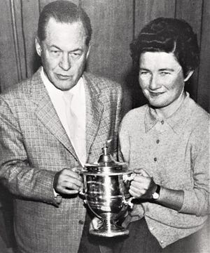 Golf great Bobby Jones stands with another golf champion, Louise Suggs.