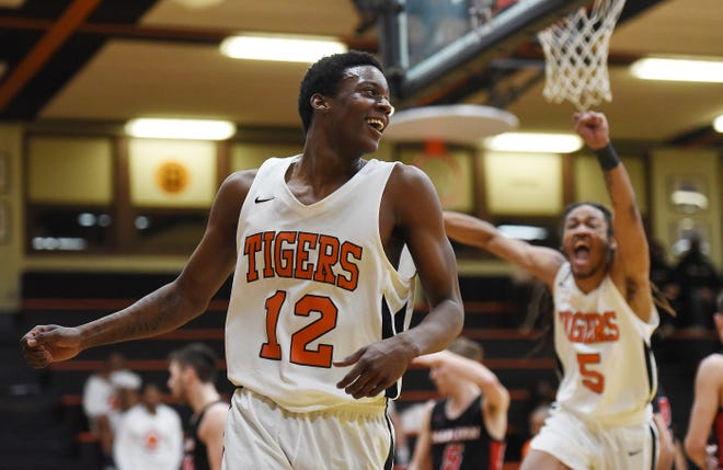Beaver Falls' Michael Conley (5) reacts after teammate D'mitri Nesmith (12) dunked the ball against Charleroi during Thursday nightÕs WPIAL Class 3A playoff game at Beaver Falls High School.