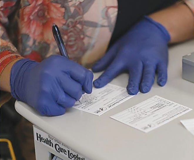 A health worker fills out a COVID vaccination card on Tuesday.