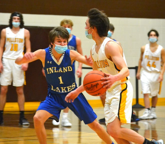 Inland Lakes junior guard Andrew Kolly (1) defends Pellston senior guard Sage LaLonde during the first half of a varsity boys basketball matchup in Pellston on Thursday.