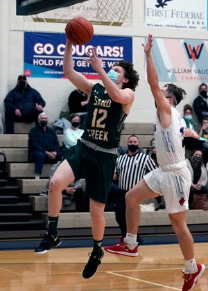 Sand Creek's Will Alexander (12) shoots a layup past a Lenawee Christian defender during the first half of Thursday's game at Lenawee Christian. The Aggies won, 78-64.