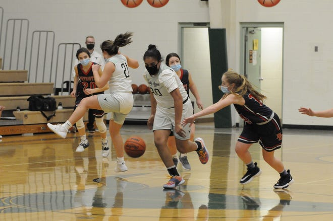 Sand Creek's Emily Carbajal (30) brings the ball up the floor as Britton Deerfield's Haylie Shiels pursues her in the second quarter of Thursday night's Tri-County Conference game at Sand Creek.