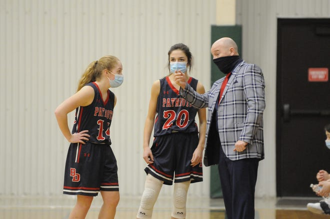 Britton Deerfield girls basketball coach Jeff Scott, right, talks to Haylie Shiels (14) and Claire Molnar (20) during the first quarter of Thursday night's Tri-County Conference game at Sand Creek.
