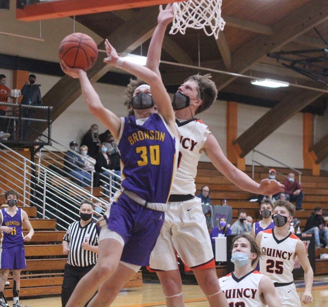 Bronson's Reagan Mayer (30) takes the ball strong to the hoop while Quincy's Kyle Rodesiler goes up high for the block Thursday night.