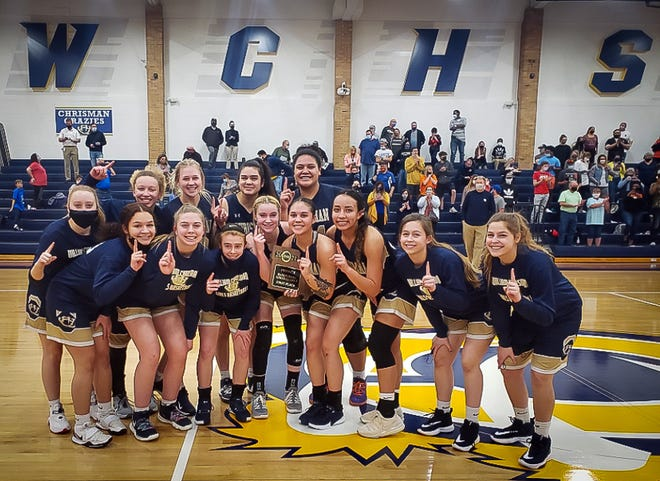 William Chrisman girls basketball players pose with the championship trophy after upsetting No. 1-ranked St. Pius X 49-45 in overtime in the Class 5 District 14 tournament final Thursday at Chrisman.