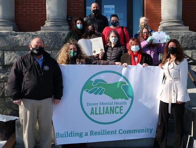 Representatives from Dover Mental Health Alliance, Recovery Friendly Work Place Initiative, and SOS Recovery Community Organization celebrate the Dover Public Library designation as a welcoming, safe and judgment-free space on, Feb. 26. First row, from left, Dover Mayor Robert Carrier, Suzanne Weete, Karen Morton-Clarke and Melissa Lesniak. Second row, from left, Library Director Denise LaFrance and Librarian Aimee Lockhardt. Third row from left: Mary Boisse, Sam Lewandowski, Heather Berube and Peggy Thrasher. Top is Drew Maranhas.