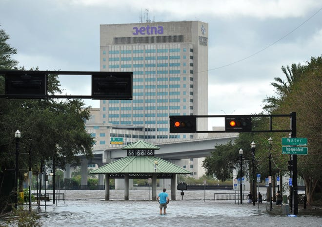 A spectator stands in the flooded intersection of Water Street and Independent Drive in this 2017 photo as floodwaters from Hurricane Irma still covered many of downtown's streets.