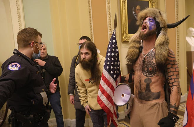 Jacob Chansley (in horns) and other protesters interact with Capitol Police inside the U.S. Capitol Building on Jan. 6, in Washington, D.C.