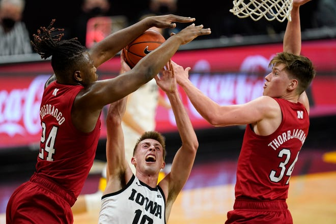 Iowa guard Joe Wieskamp, center, drives to the basket between Nebraska forward Yvan Ouedraogo, left, and guard Thorir Thorbjarnarson, right, during the first half of Thursday's game in Iowa City, Iowa.