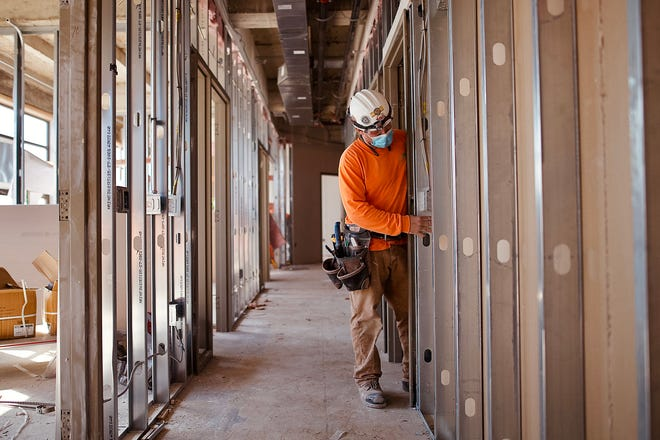 A worker inspects his drywall placement on a wall in the old administrative office area of Galesburg High School as renovations continue on Friday.