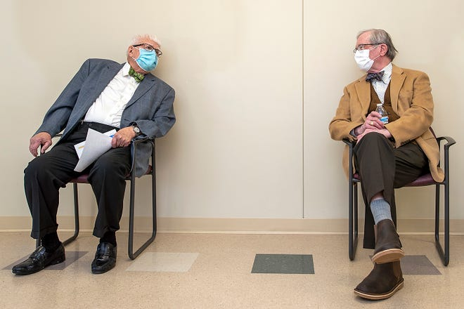 Retired doctors Robert Hickerson, left, and James King chat from a social distance after each received their Moderna COVID-19 booster vaccine at OSF St. Mary Medical Center on Friday, Mar. 5, 2021. The pair, known for their bow ties, met for the injections at the clinic to show the importance of getting the vaccine and booster.