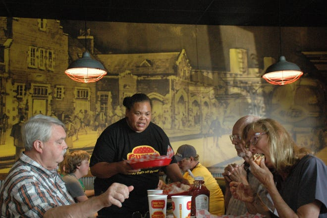 Gurty's general manager Denise Carter serves customers at the Newton restaurant, where there is not a traditional wait staff and everyone makes at least minimum wage per hour. According to a new study, the average restaurant worker in Kansas makes $20,400 annually — a salary that ranks 44th in the nation.