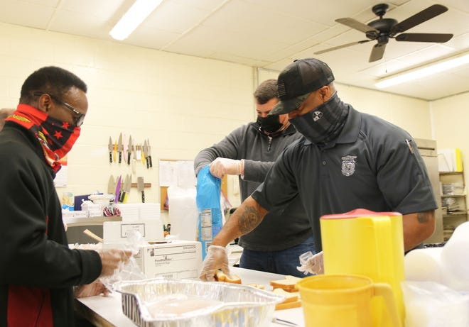 """North Carolina Highway Patrol trooper Joric """"Jax"""" Fowler, right, prepares sandwiches Friday, March 5, at Mary's Kitchen with Ret. NC Highway Patrol trooper and current abatement enforcement officer Jackie Rogers to Fowler's right and Robert Alexander across from him."""