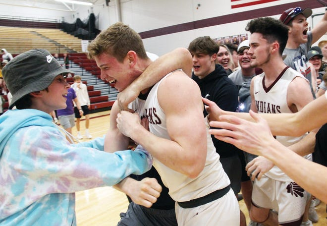 Osage senior Paven Clark is surrounded by students and junior teammate Brockton McLaughlin (back) after scoring a game-winning layup at the buzzer in a district semifinal against Versailles on March 4.
