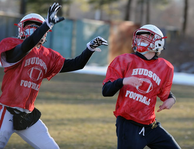 Josh Duarte and Justin Giusti look for the ball during drills at Hudson High School football practice, March 5, 2021. Duarte scored two touchdowns in the Hawks' win over Clinton on Saturday.
