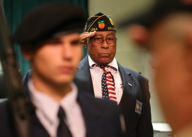 """This 2016 file photo shows Wilbur Julius saluting as """"God Bless America"""" is played during a Marion County Quarterly Memorial service in the Marion County Commission auditorium in Ocala. At these ceremonies, the Marion County veterans who died in the previous quarter are honored."""