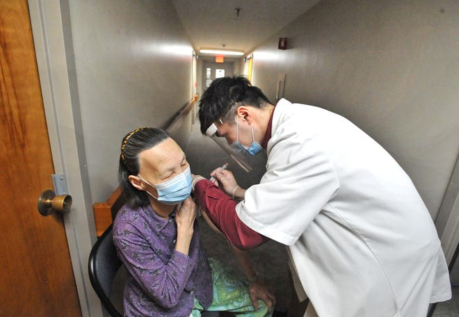 Tobin Towers resident Gui Mai receives her COVID-19 vaccine outside her room from Stop & Shop pharmacy technician Gary Lu in the Quincy Housing Authority residence Friday, March 2.