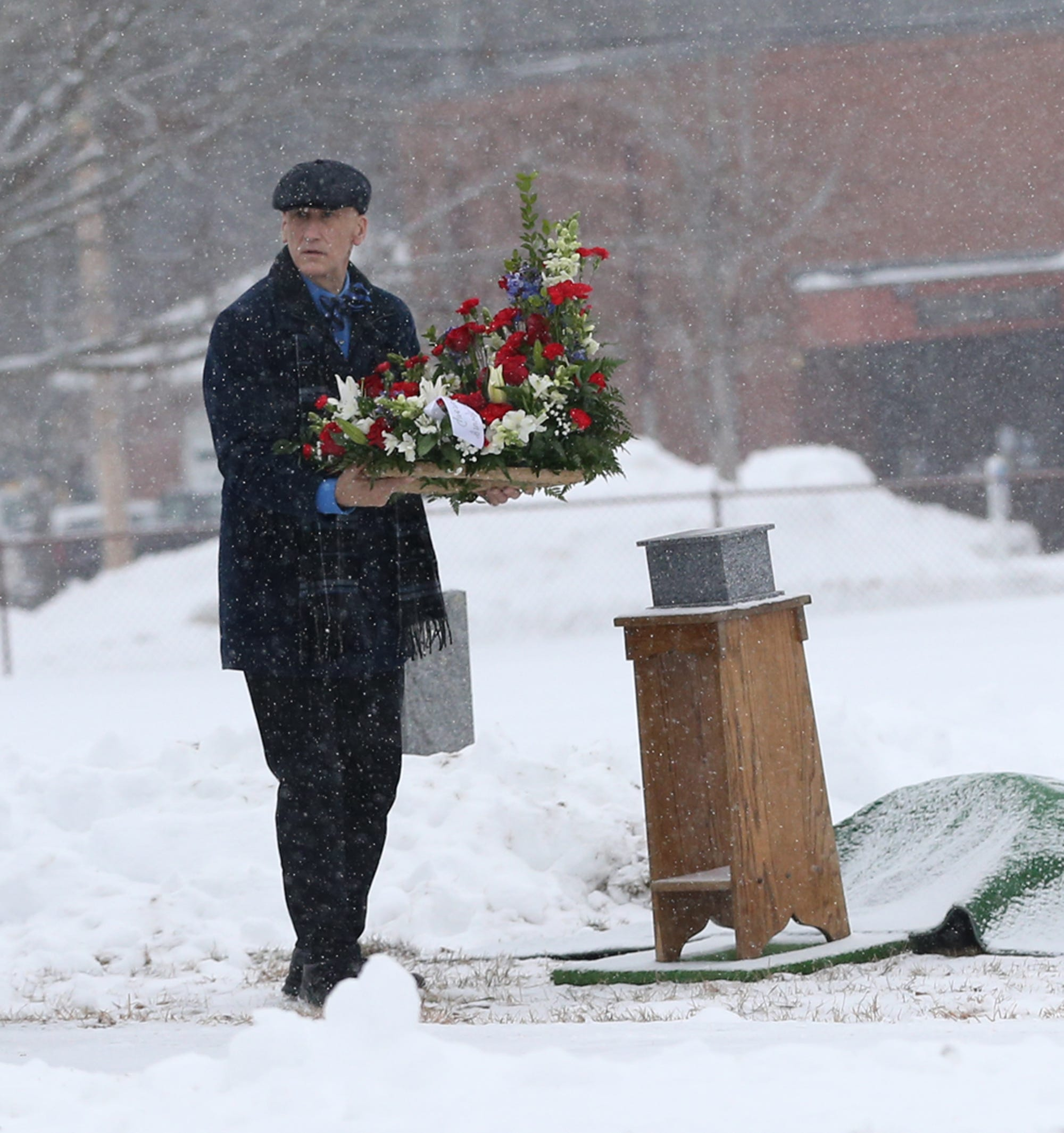 Funeral home director Jeff Pelkey puts a flower arrangement at the base of a podium resting ashes of an elderly gentleman as snow falls gently at Holy Trinity Cemetery in Somersworth, NH.