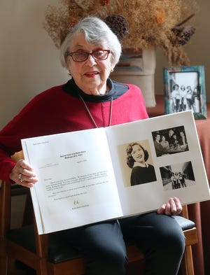 Ann Kittner, of Barrington, holds a book given to her by her family that has a section commemorating her friendship with Ruth Bader Ginsburg. She met the future U.S. Supreme Court justice when they were high school students in Brooklyn, N.Y.