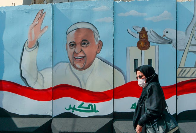 FILE— A woman walks past a mural depicting Pope Francis on a concrete wall placed by Iraqi security forces to surround the Our Lady of Salvation Church during preparations for the Pope's visit in Baghdad, Iraq, Monday, March 1, 2021. Pope Francis heads to Iraq on Friday, March 5, 2021, to urge the country's dwindling number of Christians to stay put and help rebuild the country after years of war and persecution, brushing aside the coronavirus pandemic and security concerns to make the first-ever papal visit.(AP Photo/Khalid Mohammed)