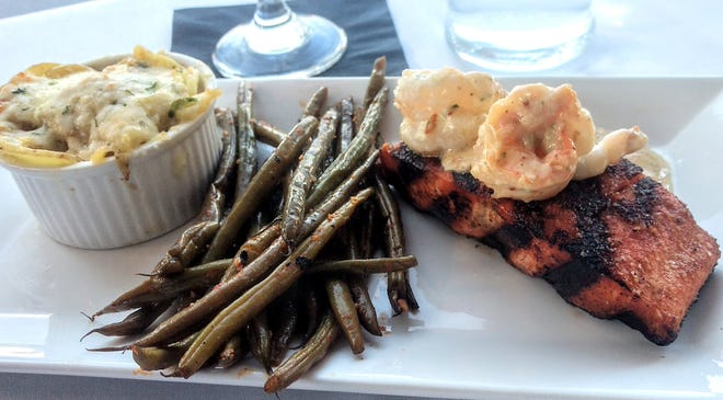 Grilled king salmon topped with Alfredo shrimp, with sides of  green beans in pepper-lemon sauce and smoked au gratin potatoes, at Scratch Steakhouse in Carrollton.