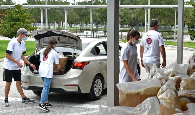 Student volunteers hand out food during a distribution at Wilkinson Elementary School. Many people who would not normally need assistance relied on such giveaways as work dried up when the COVID-19 pandemic set in. Now, those who collected unemployment benefits in 2020 may find themselves with a hefty tax bill.