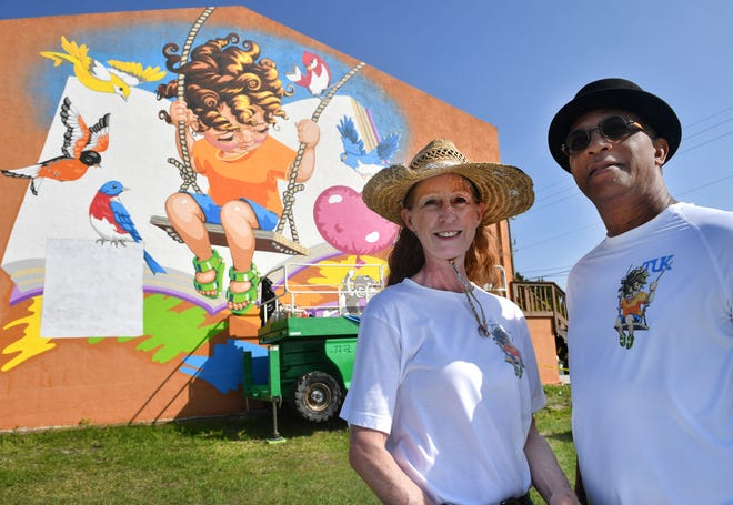 """Laura Pommier and Reggie """"Tuk"""" Wanza are putting the final touches on their mural for the First 1000 Days Sarasota project. The 30' x 30' mural has been painted on the side of the Quality TV Sales & Service building on U.S. 41 in North Port."""
