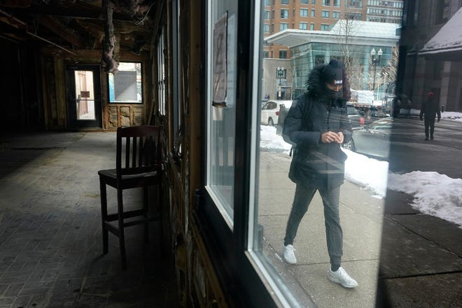 Benefits for some unemployed Illinois residents provided under an aid program targeting mostly self-employed and gig workers will be capped at 50 weeks instead of 57. In this Feb. 10 photo, a passer-by walks past an empty building that was formerly a restaurant in Boston.